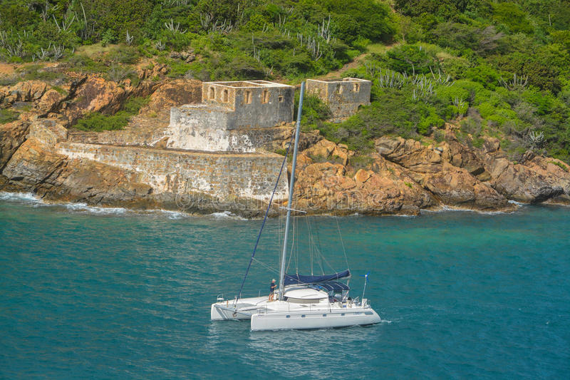 Catamaran sailing by Prince Frederikas Battery. Fort Willoughby on Hassel Island, St Thomas U.S. Virgin Islands. A catamaran sailing by Prince Frederikas stock photo