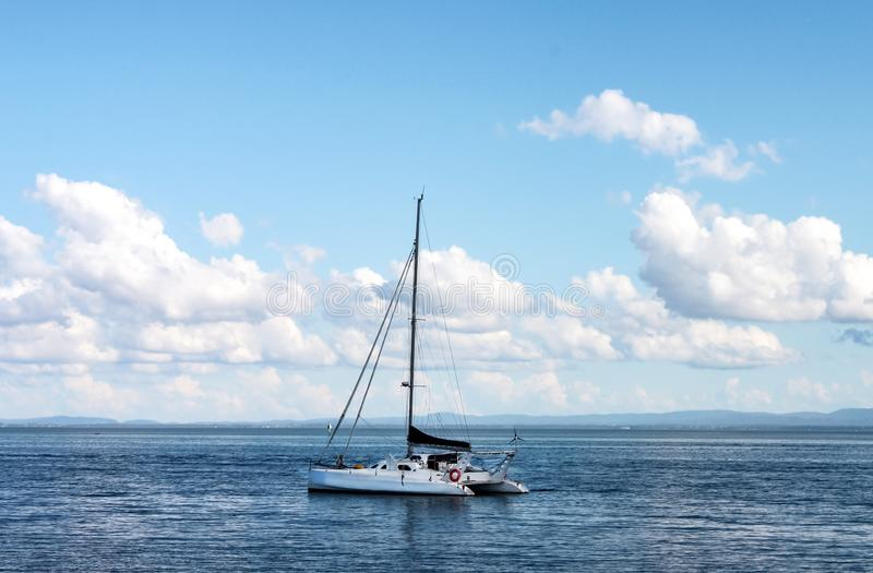 Catamaran yacht on ocean with mountains on shore on horizon under blue sky with clouds stock images