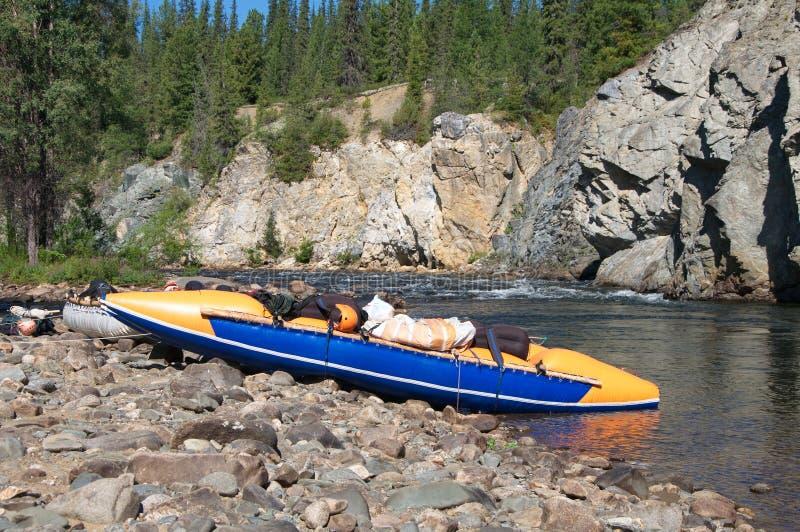 Catamaranes inflables en el banco de un río de la montaña imagenes de archivo