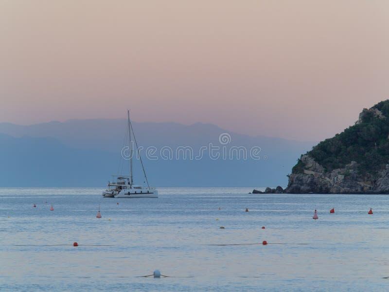 Catamaranzeilboot naast kleine eilandbergen die sil wordt verankerd stock foto's