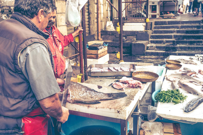 Catania, Fisherman slaughter the fish for sale fish market royalty free stock photo