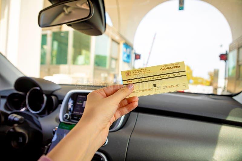 Catania, Italia - 8 02 2019: Biglietto a disposizione nell'automobile sul portone alla strada a pedaggio, Italia immagini stock libere da diritti