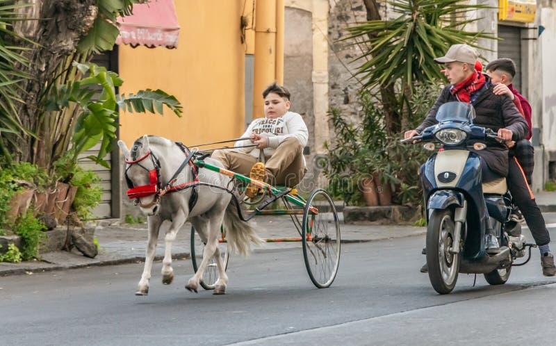 Catania Italia - 01 13 2019: Un muchacho está montando un carro con un pequeño caballo blanco y los niños están montando una moto fotografía de archivo