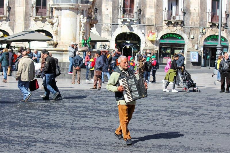 Catania, Sicilia, Italia - 10 de abril de 2019: Busker de un más viejo hombre que juega el acordeón en el cuadrado de Piazza Duom foto de archivo