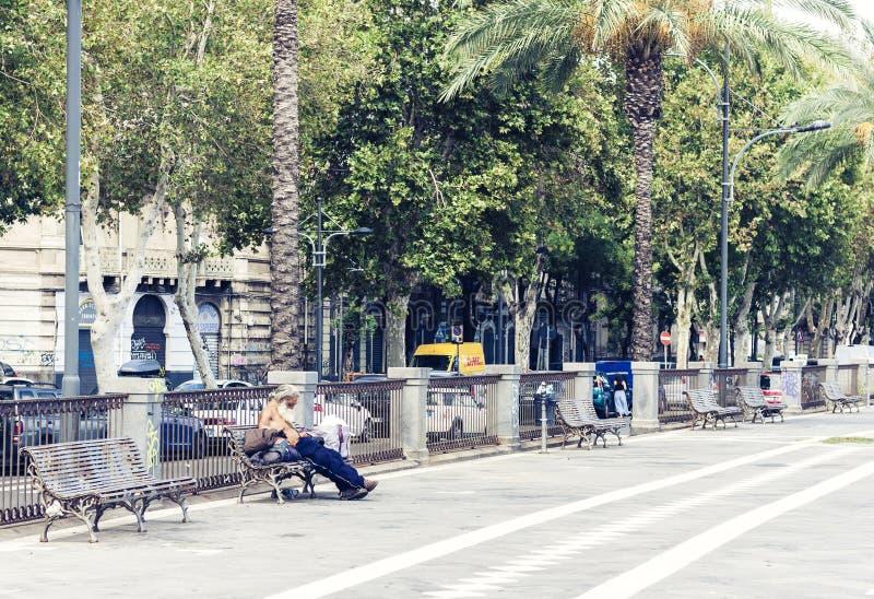"""Catania Sicilien, Italien †""""august 16, 2018: den hemlösa mannen sover på en bänk i parkerar royaltyfri bild"""