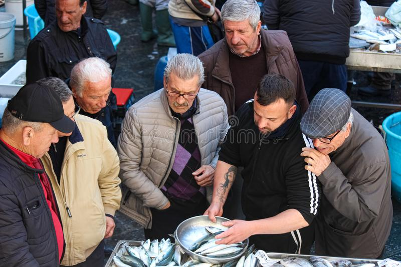 Catania, Sicily, Italy - Apr 10th 2019: Fishmonger selling fresh fish on a traditional fish market. Group of old men buyers. Is watching and giving advice stock image