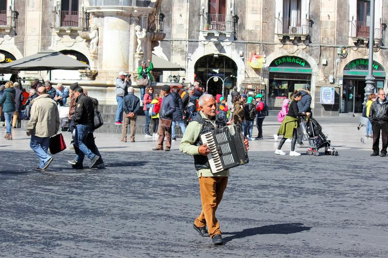 Catania, Sicily, Italy - Apr 10th 2019: Older man busker playing accordion on the Piazza Duomo square in the city center stock photo