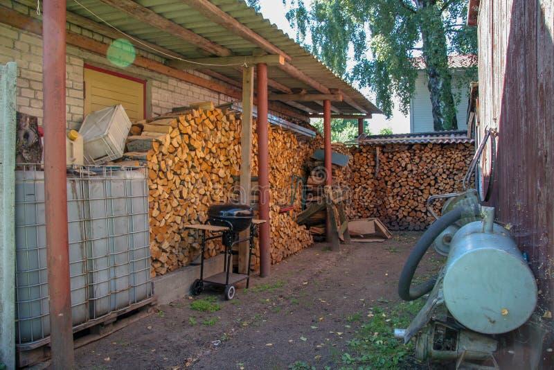 Catasta di legna alla parete della casa con una griglia e un serbatoio di acqua fotografia stock libera da diritti