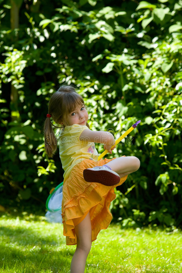 Catch the butterfly. Young little girl try to catch butterfly with a net royalty free stock images