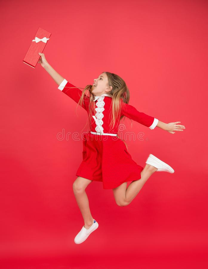 Catch it. Happy child jump for gift box. Birthday girl smile with gift in motion. Girl celebrate holiday. Shopping and stock photos