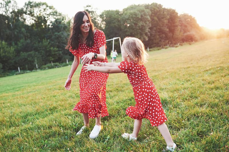 Catch me if you can. Young mother with her daughter spending time outside in such beautiful place royalty free stock photo