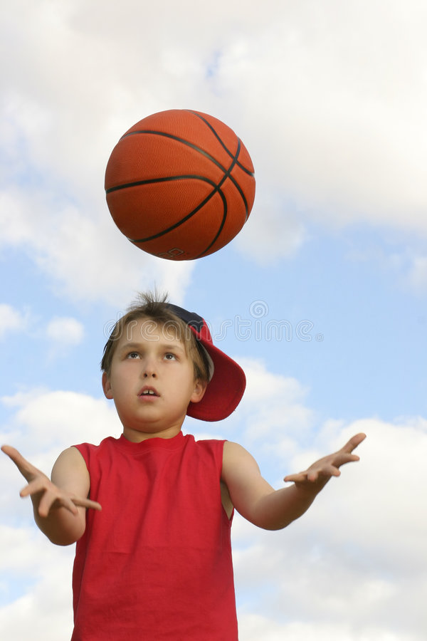Catching a ball. Boy in a red tank top catching a ball. Shot against a cloudy sky, afternoon Focus on face and ball, hands in motion 200 iso stock photo