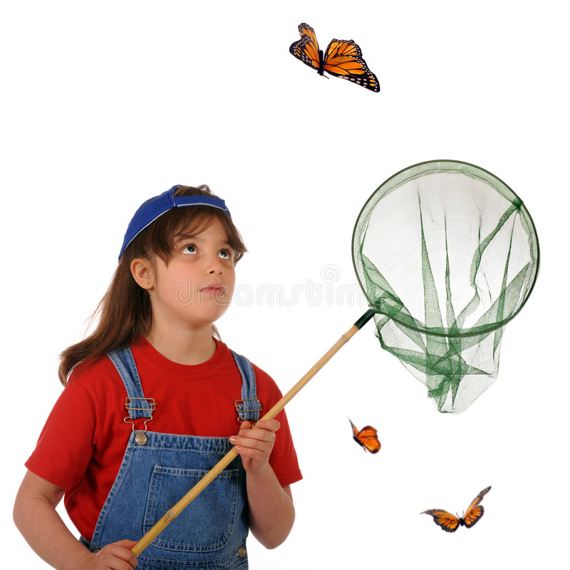 Catching Butterflies. An older elementary girl stalking a large monarch butterfly royalty free stock images