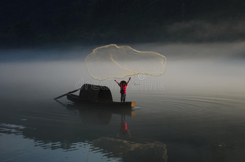 Catching fish by net in foggy river royalty free stock photos