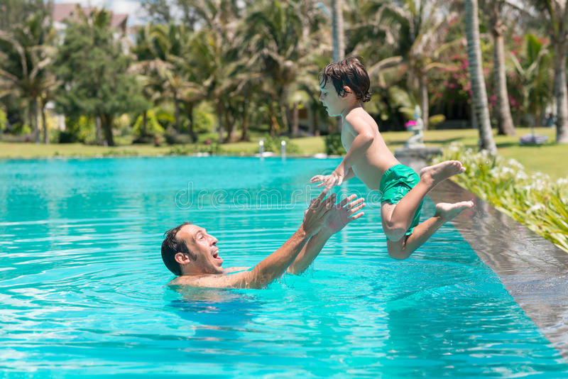 Catching. Man catching his son who is jumping into the pool royalty free stock image