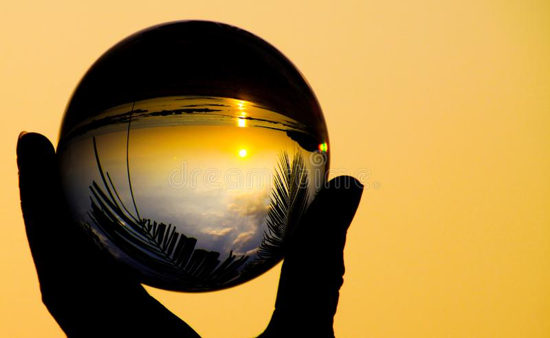 Catching sunset in crystal ball on tropical island Ko Lanta. Close up of hand silhouette holding glass sphere ball with reflection stock photography