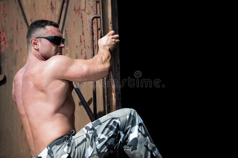 Catching A Train. Muscular Man Climbing A Ladder , Catching A Train royalty free stock image