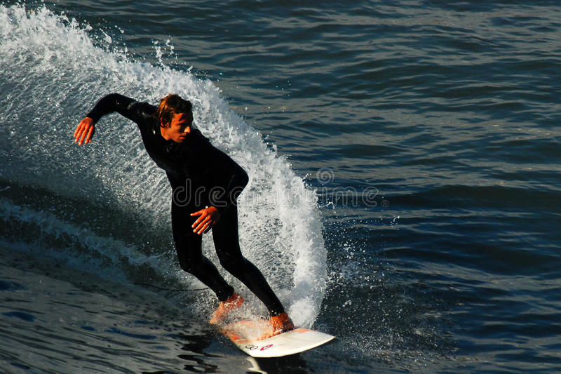 Catching a Wave. A young man cuts the surface of the water leaving a trail in his wake royalty free stock images