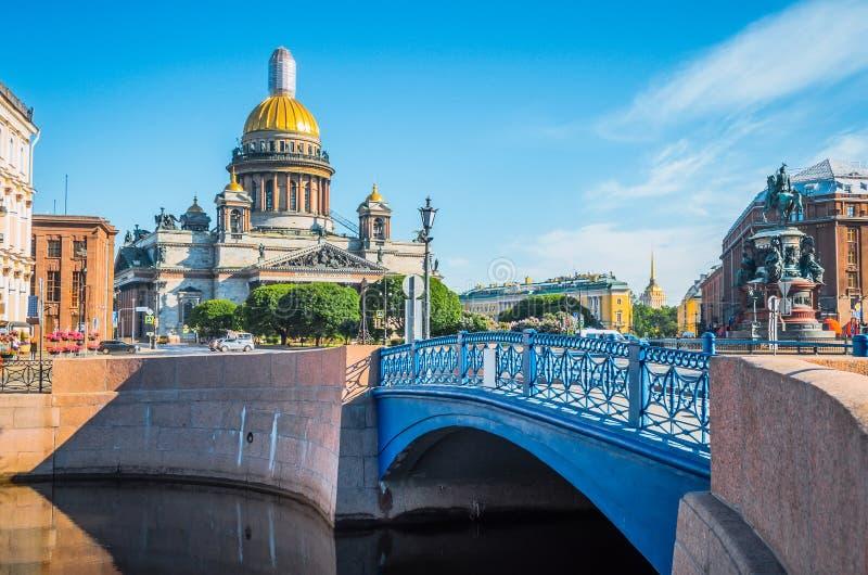 Catedral del ` s del St Isaac por la mañana en el verano, y una vista del río y del puente azul imagen de archivo libre de regalías