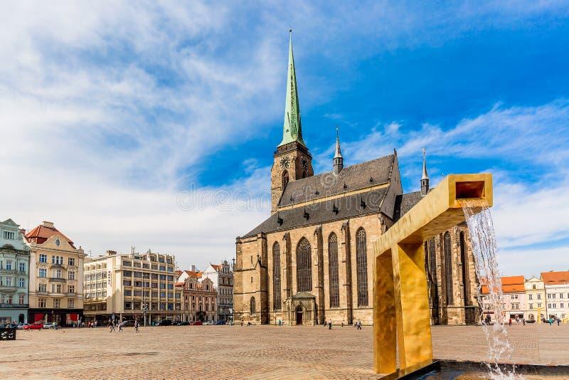 Catedral do ` s de St Bartholomew no quadrado principal de Plzen com uma fonte no primeiro plano contra o céu azul e o dia ensola imagem de stock royalty free