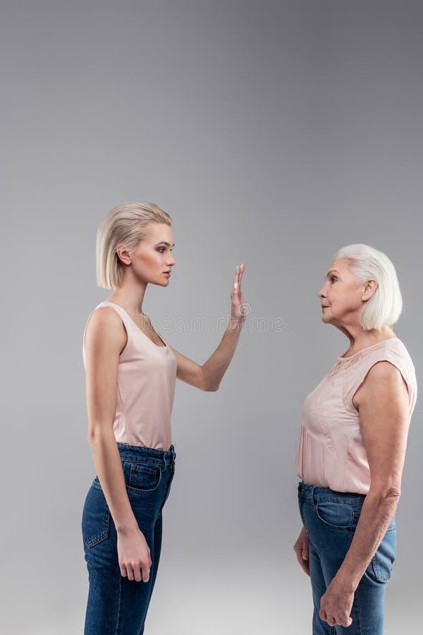 Categorisch blonde kortharig mooi meisje die haar moeder opsluiten royalty-vrije stock foto