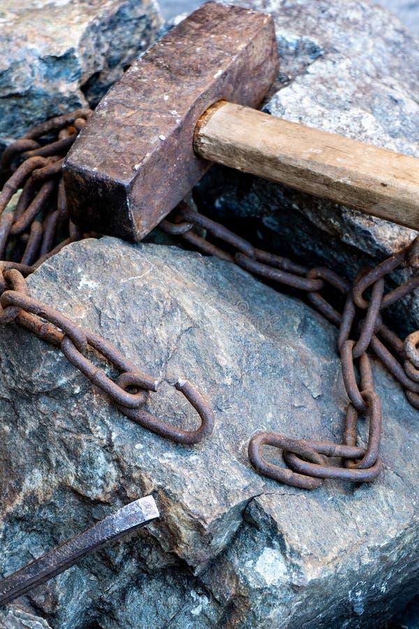Catena arrugginita e vecchio martello sulle pietre grige Una catena lacerata è un simbolo di lavoro liberato immagini stock