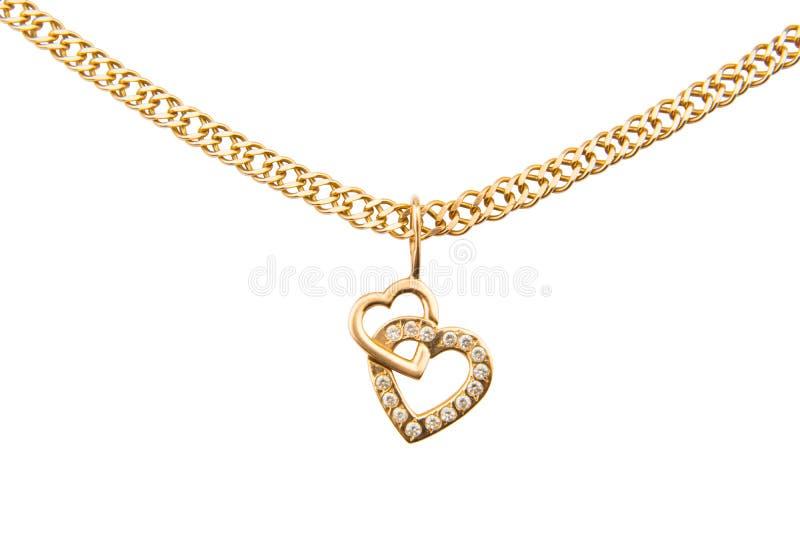 Catena dell'oro e pendente sotto forma di cuore su un backgrou bianco immagini stock