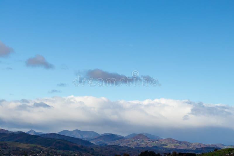 Catena montuosa in bel tempo in nuvole di pioggia di contrapposizione prima della pioggia immagini stock libere da diritti