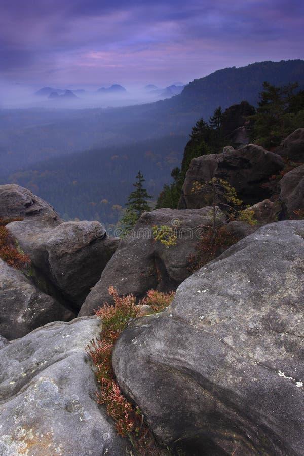 Catena montuosa boscosa dietro un picco roccioso fotografia stock libera da diritti