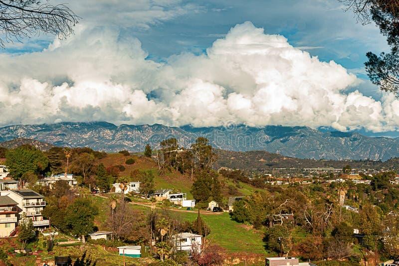 Catena montuosa delle case di Hillside con le nuvole di nimbus enormi del cumulo fotografia stock