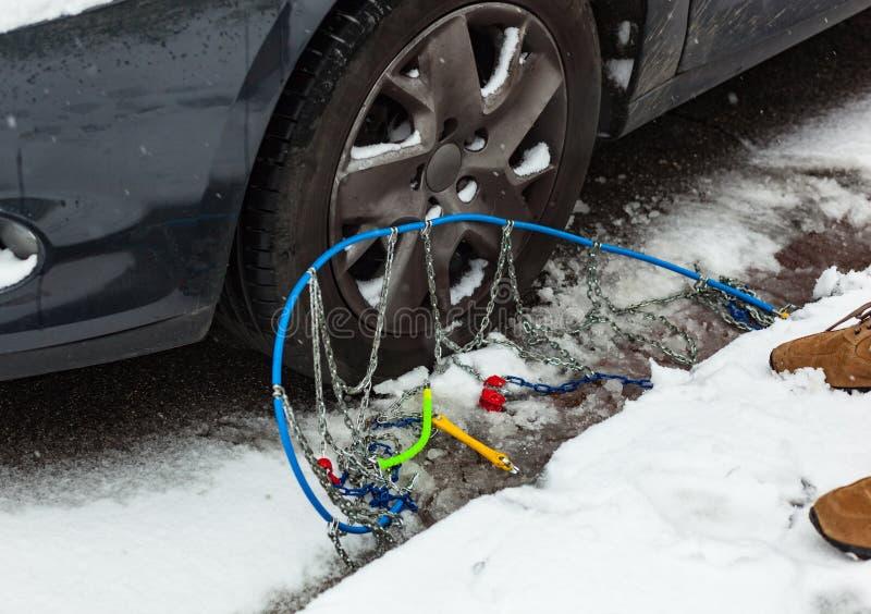 Catene di neve vicino alla gomma di automobile immagini stock