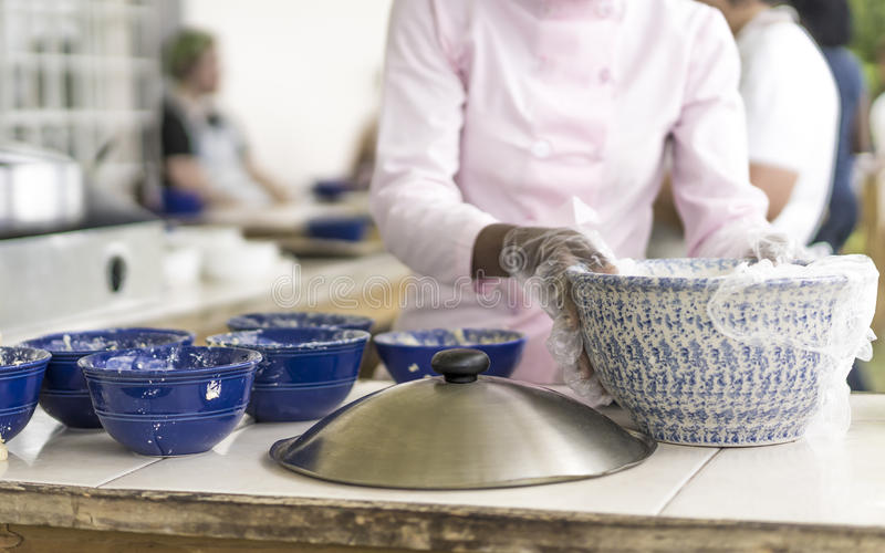Caterer preparing food on a buffet. At a restaurant or venue, closeup of her gloved hands removing plastic covering on food royalty free stock photos