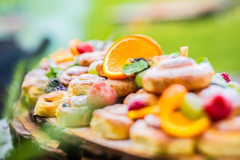 Catering buffet food outdoor. Cakes colorful fresh fruits berries oranges grapes and herb decorations stock image