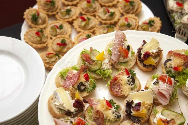 Catering, company food service, plates full of fresh tasty food and small appetizers, banquet concept, lots of small sandwiches stock photography