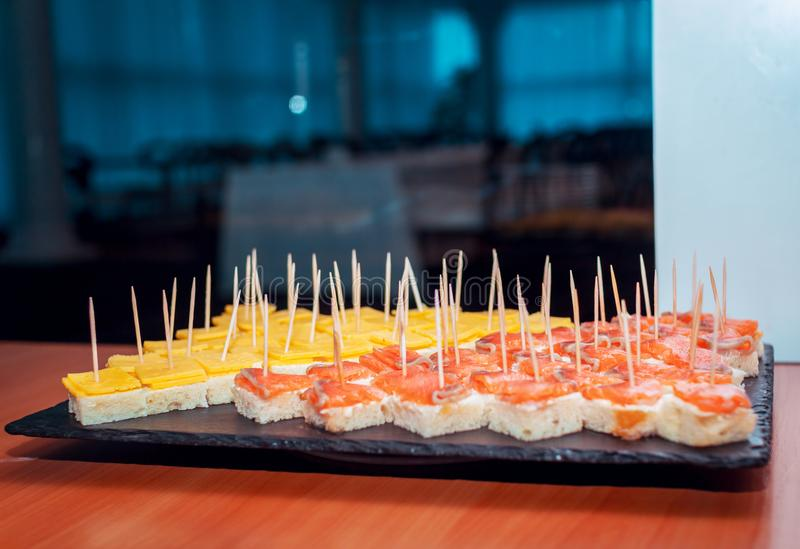 Catering food – canapes with salmon and cheese served on black stone tray stock image