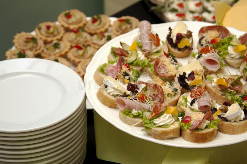 Catering, food service, plates full of fresh tasty food and appetizers, company banquet concept royalty free stock image