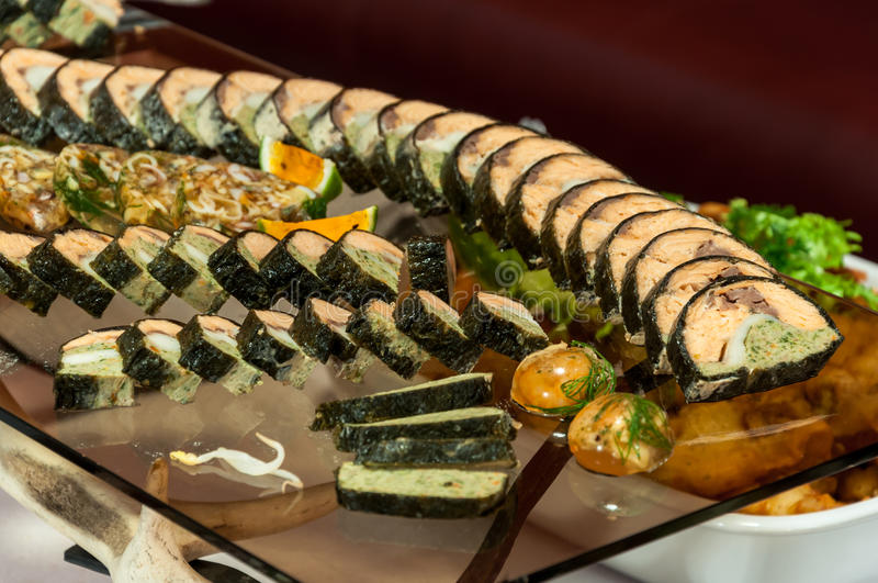 Catering food tray. Luxurious platter of catering food assortment - salmon roll cuts royalty free stock image