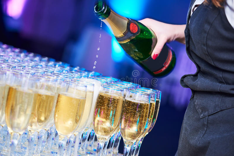 Catering at party event. Waitress pouring wine glasses in restaurant. Catering. Waitress pouring wine into glasses at party event celebration in restaurant stock image