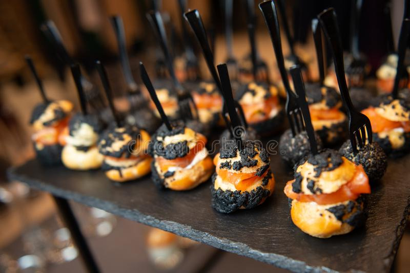 Catering in restaurant. Appetizing snacks with salmon and cheese balls in black sesame on black plate with black forks. Closeup vi stock photo