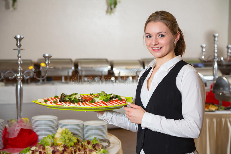 Catering service employee posing with tray for buffett stock photo