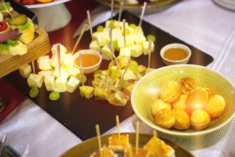 Cateringplatte appetitanregende Sandwiche auf Plastikstöcken auf einer Tabelle das Buffet stockfoto