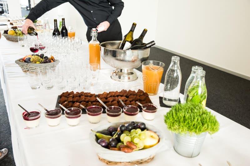 Cateringsdesserts op Buffetlijst met Mensen Dienende Wijn in B royalty-vrije stock foto's
