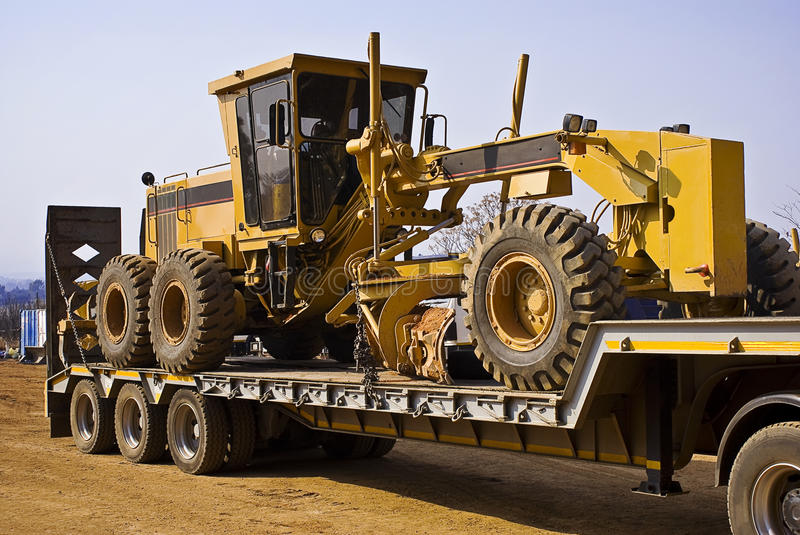 Caterpillar 140H - Chained Down. Heavy Duty Construction Equipment. Caterpillar grader, 140H, chained down, securely on the back of it's long haul transporter stock images