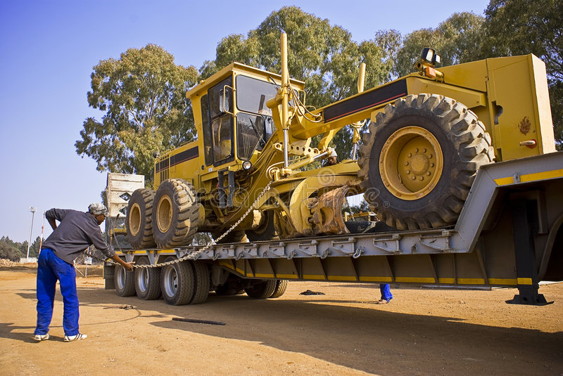 Caterpillar 140H - Chained Down. Heavy Duty Construction Equipment. Chaining this huge Caterpillar 140H grader onto the back of it's long haul transporter stock image