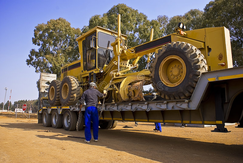 Caterpillar 140H - Chained Down. Heavy Duty Construction Equipment. Chaining this huge Caterpillar 140H grader onto the back of it's long haul transporter stock photos