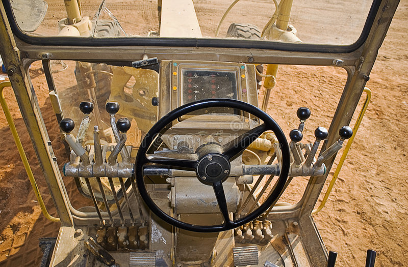 Caterpillar 140H Drivers View. Drivers perspective sitting in the cockpit of a Caterpillar 140H grader. Note the missing knob at the left hand group of lever stock photos