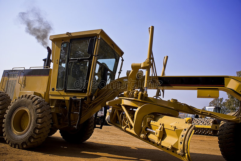Caterpillar 140H Driving. Caterpillar 140H grader operator driving thru the frame royalty free stock image