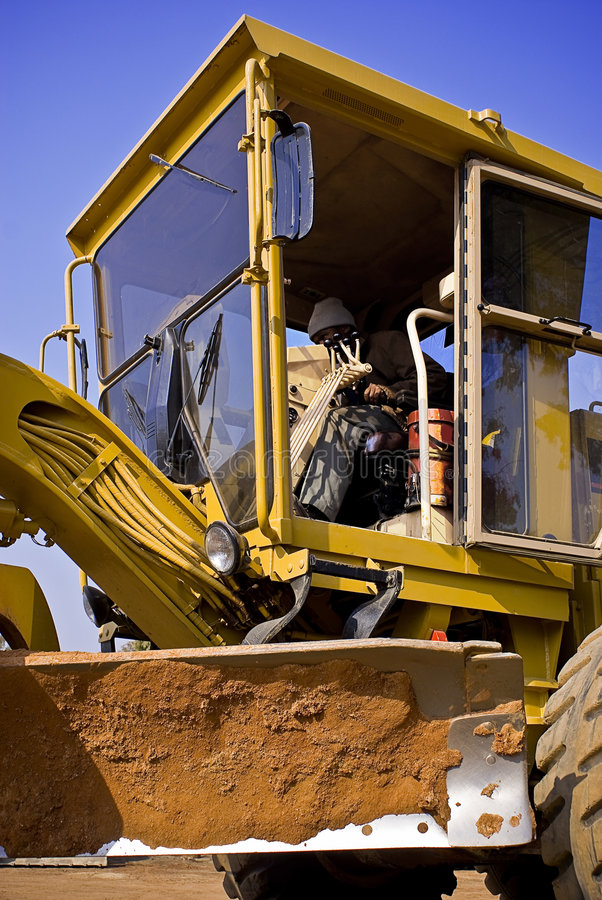 Caterpillar 140H - Grader Driver. Heavy Duty Construction Equipment. Grader Operator going thought the motions. See the residual red earth left behind on the stock photography