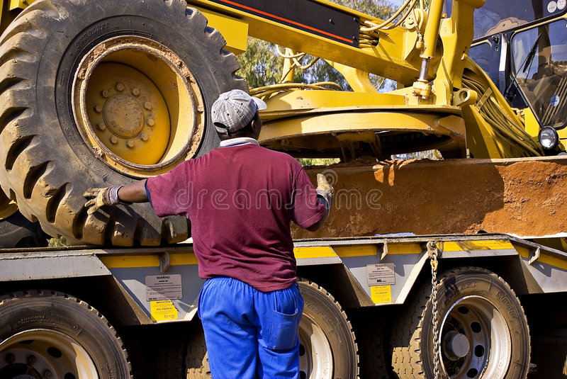 Caterpillar 140H Loading. Heavy Duty Construction Equipment. Seen here directing the loading of this huge Caterpillar 140H grader onto the back of it's stock image