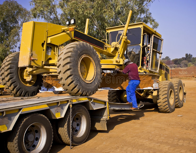 Caterpillar 140H Transporter. Heavy Duty Construction Equipment. What a job an a half. Getting this huge Caterpillar 140H grader onto the back of it's long haul royalty free stock photo